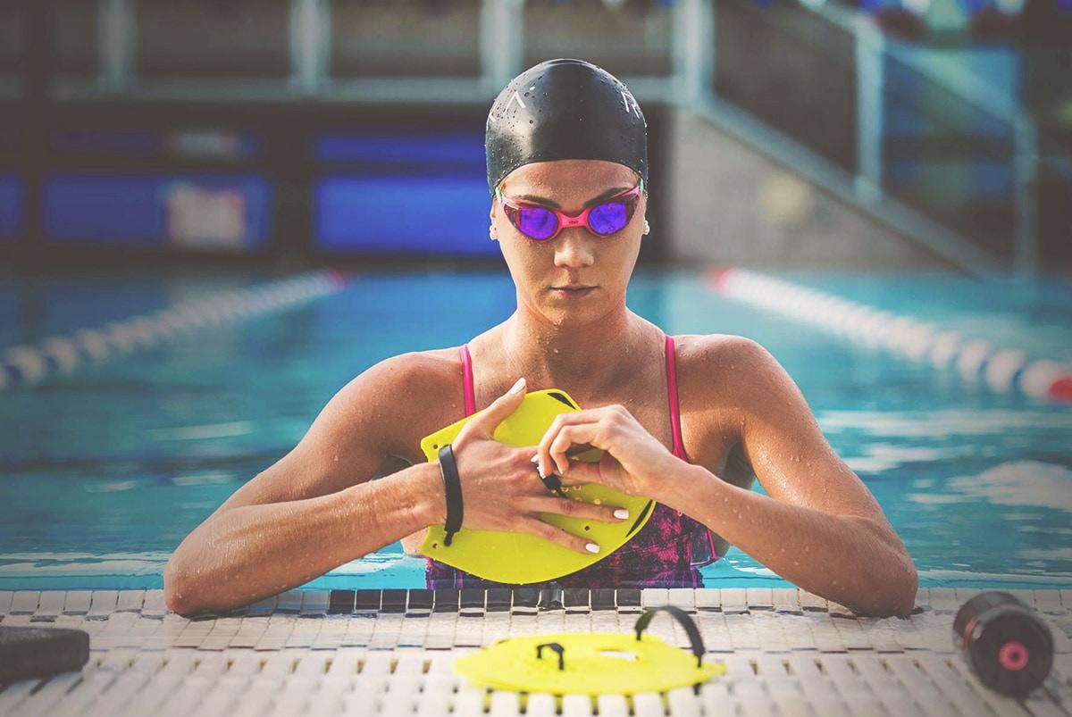 Female swimming wearing the pro swim hand paddles